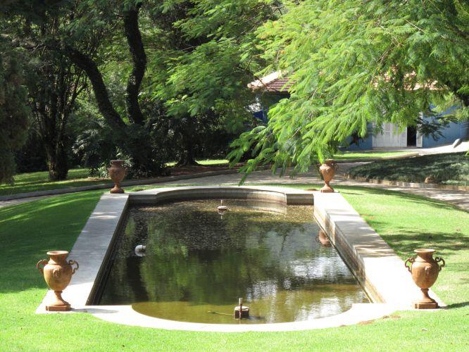 Ao lado da casa, um espelho dá água de linhas neoclássicas tem fonte e foi adornado com ânforas de terracota