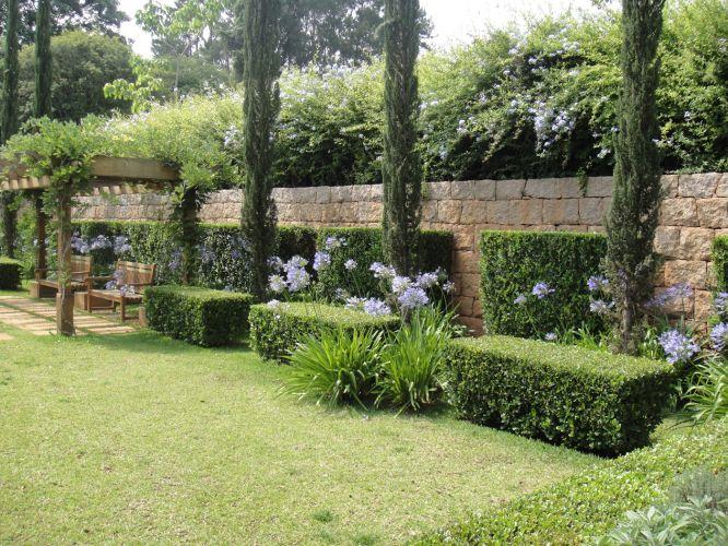 Do alto do muro de pedra, as plantas despontam criando mais área de sombreamento e fundo para o jardim. Os ciprestes trazem verticalidade ao conjunto e mantêm o toque provençal