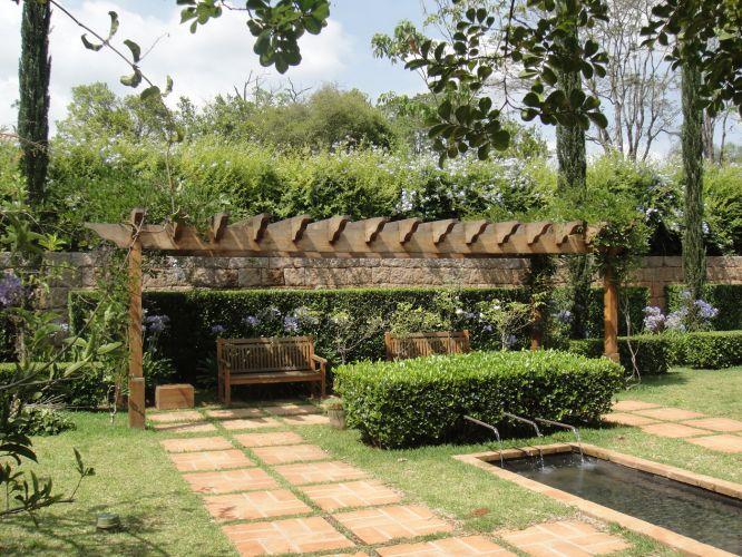 Graças à poda, diferentes volumes e alturas dão movimento ao jardim, que fica mais fresco com o espelho d'água