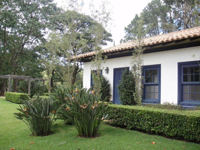 O viburno podado forma uma cerca viva em torno do gramado. Em primeiro plano, touceiras de estrelítzia proporcionam cor ao jardim
