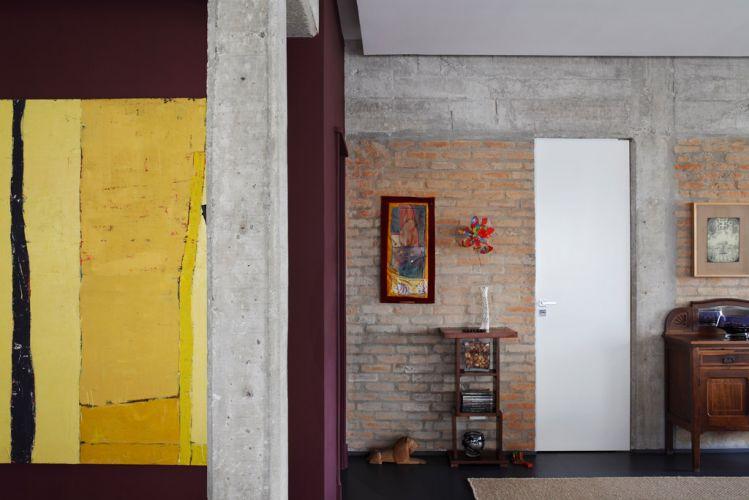 O pilar de concreto e as paredes de tijolo aparente contrastam com o quadro amarelo do artista José Bernnô. Sobre a cômoda antiga, quadro com desenho em nanquim de Alex Ceverny. A porta pivotante, acabada com laca branca, dá acesso ao lavabo