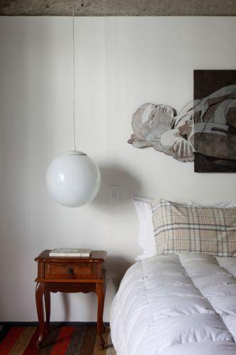 O dormitório principal apresenta concreto aparente na parte superior da parede e pintura branca na parte inferior. O criado mudo antigo, herança de família, faz contraponto com a luminária moderna, da Reka iluminação. O quadro é de Luiz Paulo Baravelli