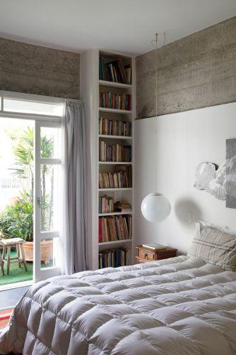 Voltado para o terraço, o dormitório principal recebe luz natural intensa através da porta-janela. Na lateral, coluna de laminado com prateleiras deixa todos os objetos e livros à mão