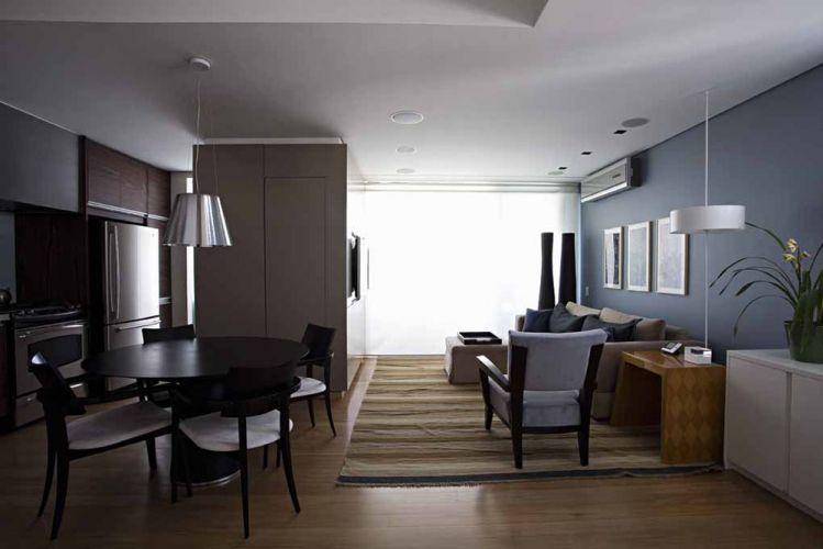 A tinta acrílica azul super lavável da Sherwin Williams dá o tom masculino ao living integrado à cozinha. O bloco do lavabo, feito com painel de MDF laqueado, divide o ambiente e também serve de apoio à TV. Detalhe: a porta de acesso é camuflada e abre por toque. No forro de gesso, além da iluminação, há caixas de som B&W embutidas. No estar, sofá Brentwood, tapete Clatt, e gravuras da Galeria Gravura Brasileira
