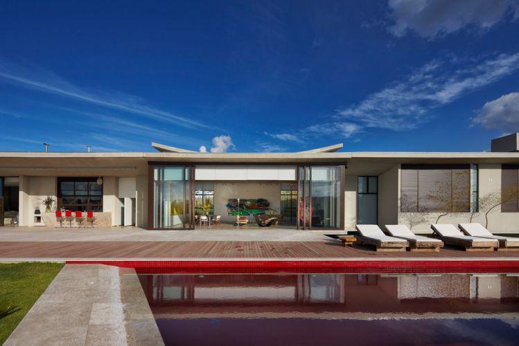 Grandes aberturas envidraçadas integram a casa aos espaços de lazer