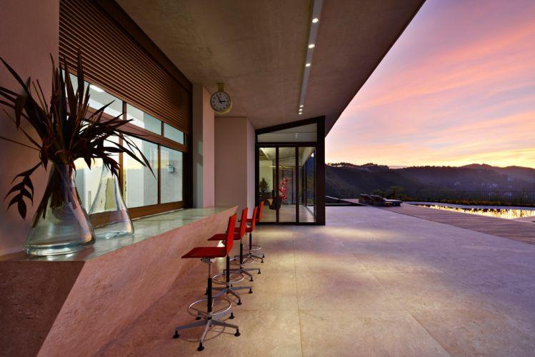 O bar da piscina abre-se para ampla varanda e espaços de recreação, voltados para a face oeste