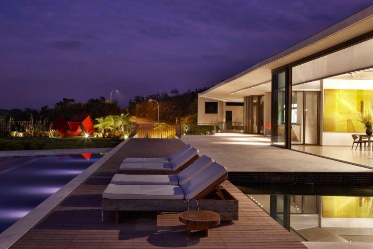 A foto evidencia a transição entre a área interna, a varanda coberta e o deck até chegar ao gramado e à piscina