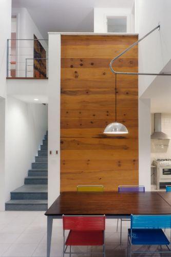 Na escada que leva aos dormitórios foi usado granito cinza andorinha, e no painel vertical do hall, madeira peroba mica