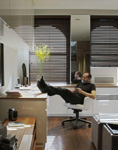 Uma paleta de cores mais sóbria e muitos armários tornaram o apartamento de 46 m² de Michael Pozner, executivo que trabalha em casa, um lugar organizado. A parede atrás da escrivaninha tem peças altas de acabamento brilhante que contribuem para ampliar o espaço