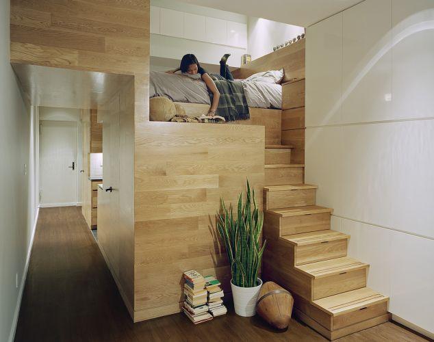 O módulo revestido de madeira é a solução mais ousada aplicada no apartamento. As escada que levam à cama são, na verdade, gavetas. Sob o quarto há um closet. Nas parede lateral aos degraus e sobre a cama, mais armários