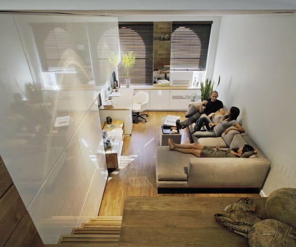 Vista do estar e área de trabalho a partir do dormitório. A disposição do mobiliário define o espaço do living, diferenciando-o do restante do apartamento