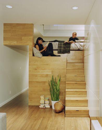 A foto mostra o acesso ao dormitório, instalado no módulo que ainda acomoda o closet, a cozinha e o banheiro, além de armários