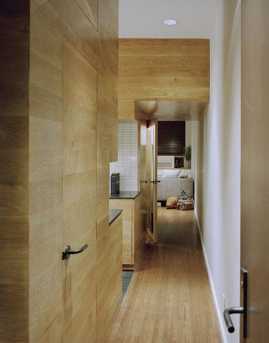 O corredor de entrada passa pelo módulo e chega à sala de estar e trabalho no fundo. A primeira porta à esquerda é do banheiro