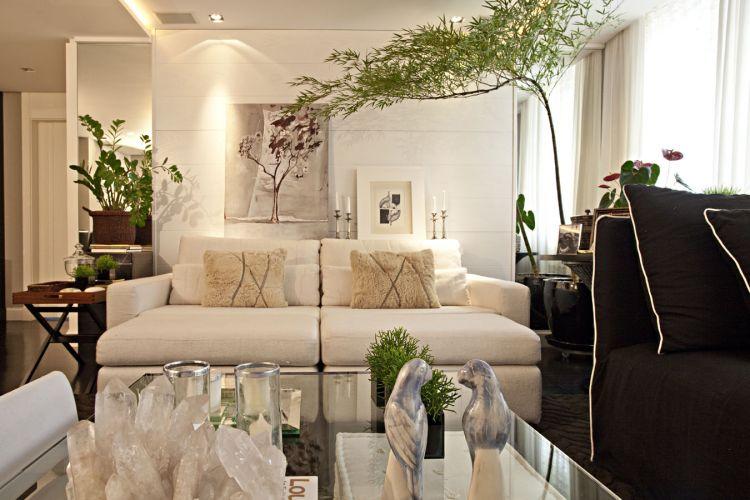 À esquerda do sofá, mesa-bandeja da Vermeil; à direita, a mesa lateral da Casual foi decorada com porta-retratos. A tela atrás do sofá é da artista plástica Pama Loiola