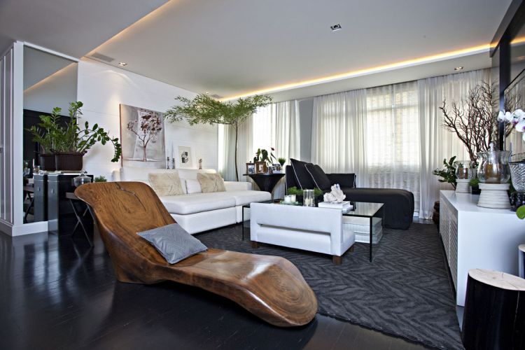 A chaise longue de madeira, assinada pela designer Monica Cintra, introduz cor e rusticidade ao ambiente onde predomina uma paleta de cinzas e preto. O piso de tábuas corridas de ipê foi ebanizado