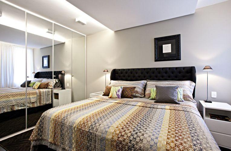 No quarto do casal, sobre a cama, um rebaixo no forro de gesso abriga fitas de LED para iluminação indireta. O guarda-roupa tem portas espelhadas e a cabeceira da cama foi executada em chanton de seda, do Empório Beraldin. Sobre a cama, a gravura na moldura preta foi feita por Gustavo Rosa para a proprietária do apartamento. O abajur é da Puntoluce