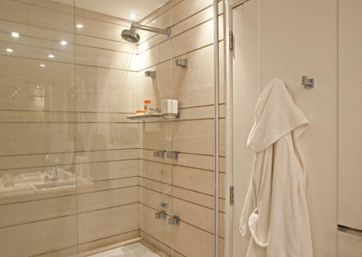 No banheiro da suíte, o espaço do box foi revestido com limestone tratado com resina impermeabilizante