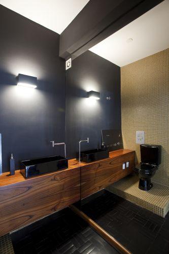 Chique, o lavabo é todo preto - parede com pintura, piso de taco ebanizado, louças pretas. Exceção é a parede com pastilhas bege-douradas da Colormix. Destaque para a parede inteiramente coberta por espelho