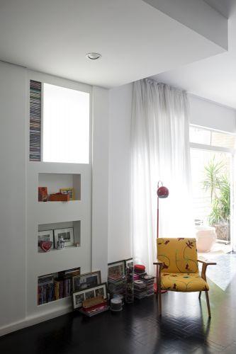 Detalhe do living, com nichos recortados na parede para guardar vários objetos, inclusive CDs. Um dos destaques da ambientação é a cadeira amarela de Zanine Caldas, da Desmobília
