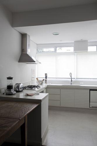 A cozinha foi transferida para o espaço anteriormente ocupado pela área de serviço. Piso e bancada de granilite