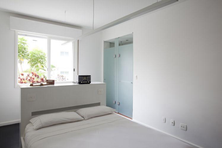 A suíte de hóspedes tem solução criativa: atrás da cabeceira da cama foi instalada uma bancada com cuba servindo ao banheiro com divisória de vidro entre o box e o sanitário