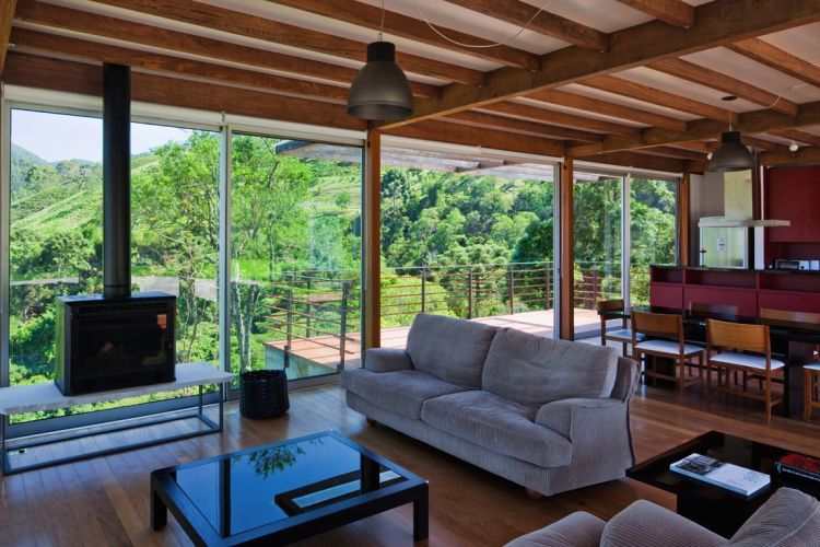 Apesar de toda a transparência conferida pelo fechamento de vidro, o interior da construção é acolhedor. A presença da madeira nos acabamentos contribui para o efeito, enfatizado pela paisagem