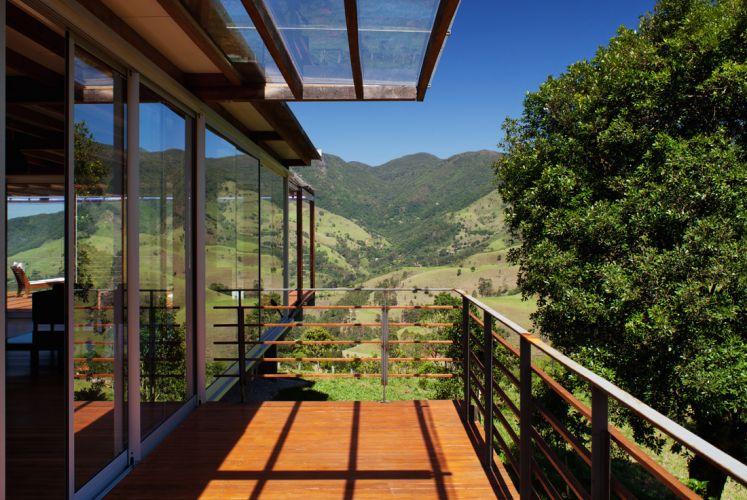 O living prolonga-se pela varanda, protegida por guarda-corpo de metal e madeira e pela continuação da cobertura, com estrutura de madeira e fechamento de policarbonato