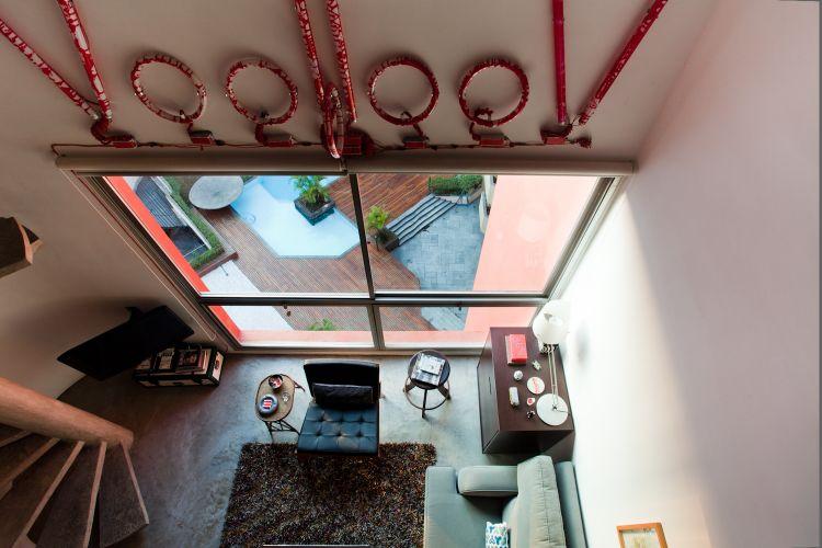 O luminoso feito pelo artista plástico francês Stéfhane Malysse fica sobre a grande janela que ilumina os dois andares do apartamento. No centro da foto, poltrona preta do designer Fernando Jaeger
