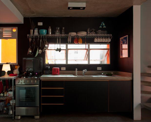 Na cozinha, parede e gabinete pretos. Sobre a janela, prateleiras industriais da Metal Stock para organizar louças, panelas e talheres. A bancada de concreto tem 2 m (largura) por 70 cm (profundidade). O tampo é mais fundo para que a pia sirva para apoiar eletrodomésticos e ainda sobrar espaço para preparar alimentos. Um abajur branco do Etna decora o móvel metálico que funciona como despensa