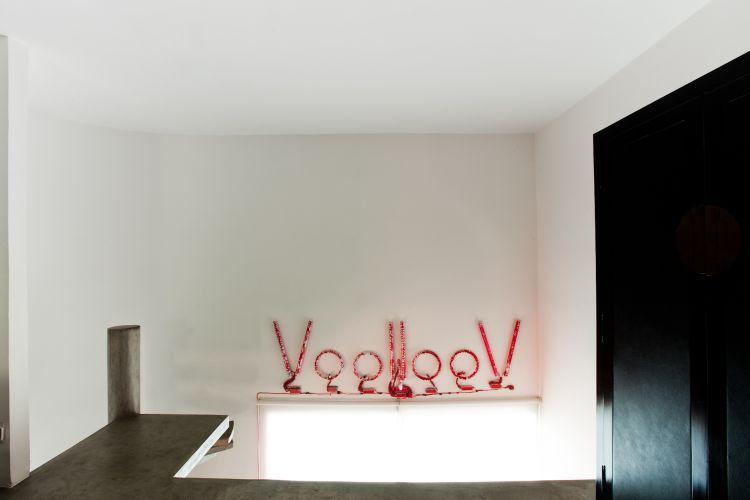 Da cama, é possível ver um luminoso feito pelo artista plástico francês Stéfhane Malysse. A peça é feita de lâmpada fluorescente convencional e pintada com tinta de vitral vermelha