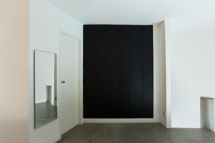 Para acessar o closet instalado na suíte, uma porta preta de chapa metálica pintada. Do lado esquerdo, a porta que dá acesso ao banheiro