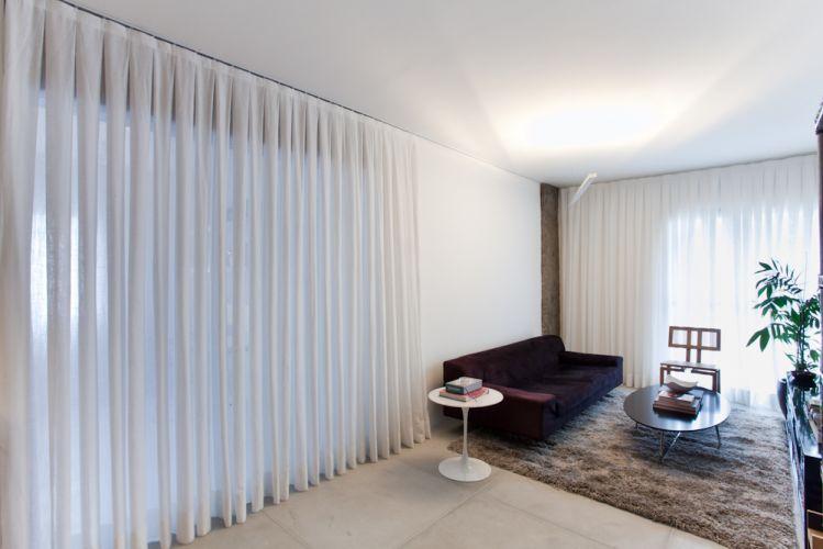 O espaço do estar em estilo contemporâneo tem apenas o necessário: sofá de camurça roxa, tapete neutro da Leroy Merlin, mesinha lateral Saarinen e cadeira desenhada por Juliana Llussa. Destaque para a cortina branca em gaze de linho que separa o ambiente do home-office. A luminária é da Reka