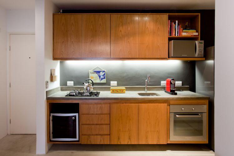 A iluminação embutida na parte superior dos armários em freijó destaca a pintura da parede em tom de cinza chumbo
