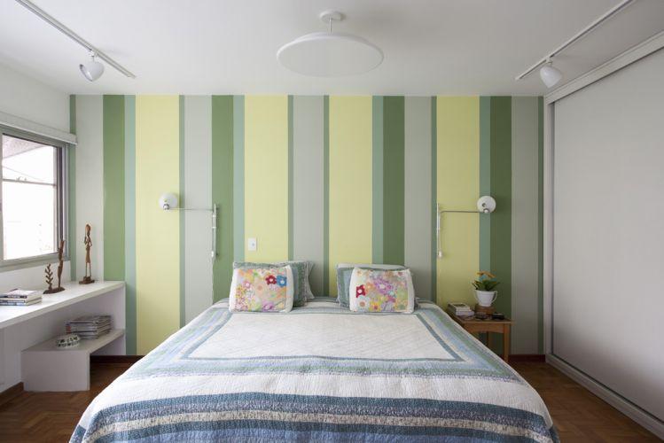 Na suíte do casal a cama foi centralizada e ganhou bastante destaque contra a parede com pintura listrada (tintas Suvinil). Suave, a iluminação é feita pelo plafon redondo, pelos spots orientáveis instalados em trilhos e pelas duas arandelas instaladas ao lado da cama