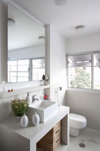 O banheiro do casal tem linhas modernas e revestimentos claros. Destaque para a bancada construída em concreto e revestida com material cimentício branco (NS Brazil) e para os gabinetes sem portas. Louças e metais sanitários são da Deca