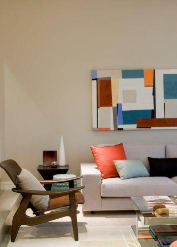 No living, a base (composta de paredes, sofás e piso) tem tons neutros; o colorido fica por conta das almofadas e do quadro de Flávia Brunetti