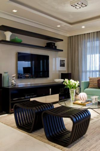 Os dois bancos pretos com desenho original em linhas arredondadas do Empório Vermeil dão um toque diferenciado ao home theater do apartamento decorado por Marília Veiga