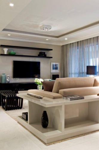 Conforto e harmonia são a tônica do home theater que possui alguns diferenciais, como o aparador branco executado pela Takae Arte. O móvel contorna o sofá e serve de apoio para objetos decorativos