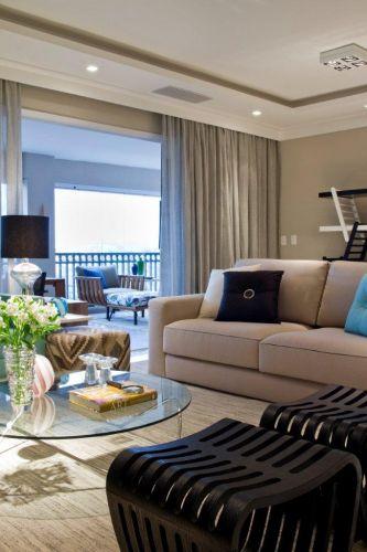 No ambiente de estar destacam-se o móvel para TV e equipamentos de som executado pela Takae Arte, a poltrona verde claro do Empório Vermeil e a mesa de centro com tampo de vidro da Futton Company. O tapete é da Fenícia e, o pufe revestido de kilim, da By Kamy. Os dois bancos em ripas com desenho em linhas curvas são do Empório Vermeil. O sofá da Breton completa o ambiente criado por Marília Veiga para um apartamento de 200 m² em Guarulhos (SP)