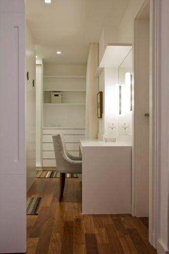 Na suíte do casal, o espaço entre os dois closets foi ocupado por um recanto de beleza para a mulher. Cadeira Empório Vermeil; tapete By Kamy