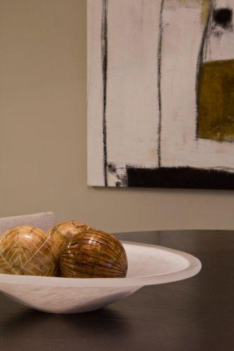 O centro da mesa de jantar é decorado por um prato de cristal com esferas de madeira, em sintonia com o ambiente