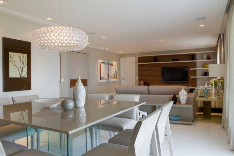Em primeiro plano, mesa de jantar e cadeiras, da Brentwood, iluminados por um pendente da Lustreco. Ao fundo, o home theater, com painel e prateleiras da Marcenaria Dantones