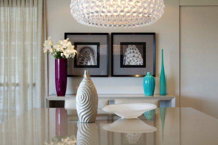O vaso de cerâmica sobre a mesa é da L'oeil. Os coloridos (púrpura e turquesa) que decoram o bufê, ao fundo, são da Futton Home e os quadros são da Moldura Minuto
