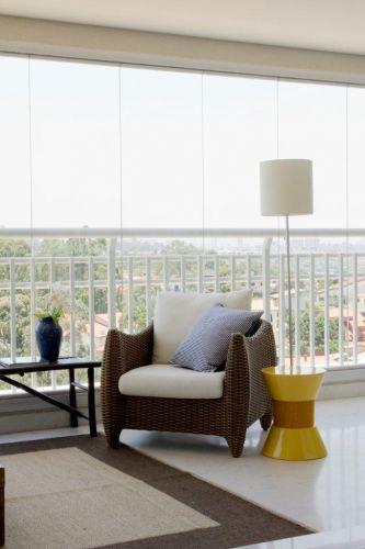 A varanda é tão espaçosa que permitiu a criação de uma sala externa, quase que ao ar livre. A poltrona é da Casual Móveis, o banco de madeira pintada e as almofadas, da Empório Beraldin e o tapete de fibras naturais é da Fanucchi Tapetes