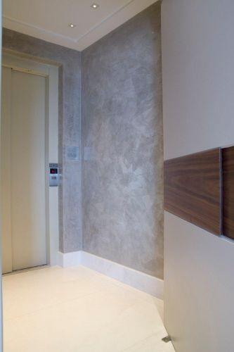 Porta de entrada com detalhe de madeira nogueira. Ao fundo, é possível ver o hall do elevador
