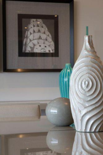 Em primeiro plano, vaso de cerâmica da L'oeil, centro de mesa de cristal da Roberto Simões e vaso turquesa da Futton Home. Ao fundo, quadro da Moldura Minuto