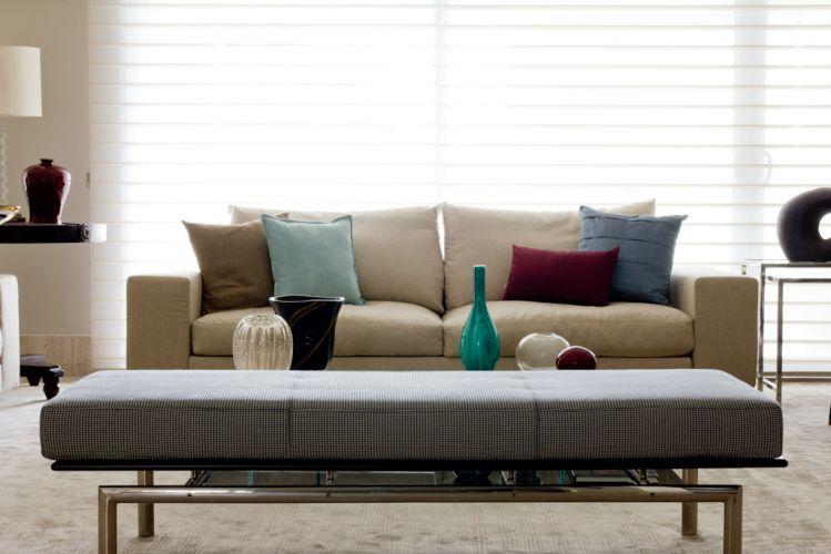 Em primeiro plano, o banco da Artefacto. Ao fundo, o sofá da Flexform com almofadas do Empório Beraldin e as cortinas Sillouette, em tela de poliéster, da Luxaflex. O projeto de decoração do apartamento no bairro Panamby, em São Paulo, é assinado pela designer de interiores Marília Brunetti de Campos Veiga