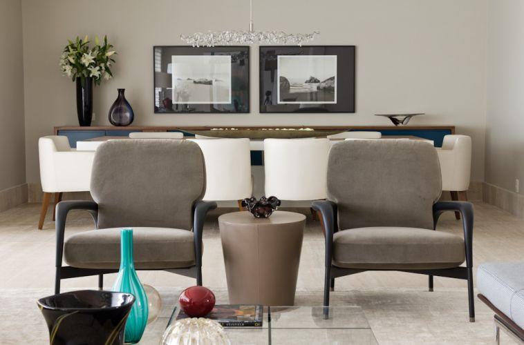 As duas poltronas da Atrium são combinadas à mesa de apoio em couro, do Empório Beraldin. Ao fundo, o sofisticado ambiente de jantar. O projeto de decoração do apartamento no bairro Panamby, em São Paulo, é assinado pela designer de interiores Marília Brunetti de Campos Veiga