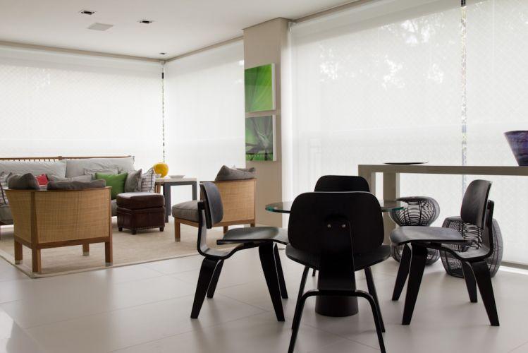 No terraço da lareira (com 30m²), a designer de interiores criou três espaços aconchegantes. O estar, ao fundo, tem sofá Gervasoni, além de poltronas e pufe da Flexform. O local para refeições foi constituído pela mesa redonda com tampo de vidro (Artefacto) e as cadeiras de madeira do Empório Vermeil. Enquanto o terceiro ambiente, para o descanso, conta com duas poltronas da Poliform. Os ambientes ganharam piso porcelanato off white, tapete oriental By Kamy e cortinas rolos na cor branca, da Luxaflex. O projeto de decoração do apartamento no bairro Panamby, em São Paulo, é assinado pela designer de interiores Marília Brunetti de Campos Veiga