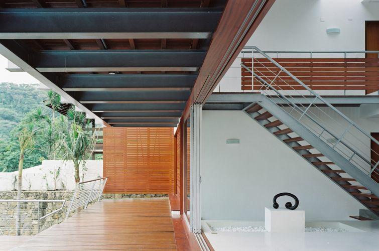 Na ampla varanda do térreo, um painel de madeira filtra a incidência do sol do poente e protege a privacidade da família. A casa projetada por Biselli Katchborian Arquitetos fica em São Sebastião, litoral de São Paulo